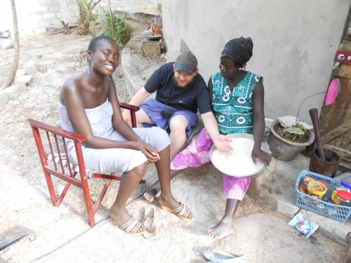 Tony with Khady and another Senegalese lady. Tony touching a bowl of rice that Khady is holding.