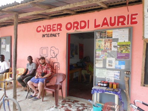 Tony sitting outside Ordi Laurie internet café, owned by Simon's European friend Laurie Marie, in Abene centre.