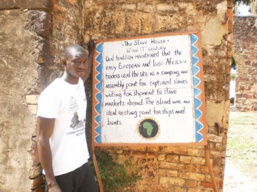 Saigou standing by a 'Slave House' sign: '16th and 17th Century. Oral tradition maintained that the early European and Luso-African traders used the site as a camping and assembly point for captured slaves waiting for shipment to slave markets abroad. The island was an ideal resting point for ships and boats.'