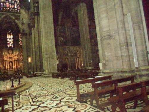 View inside the cathedral - pews, stone columns and a side altar beyond.