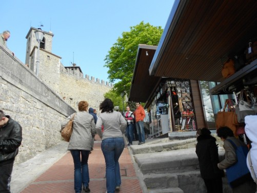 Tourists walking the steep climb up to Guaita Tower. Souvenir shops at the side.