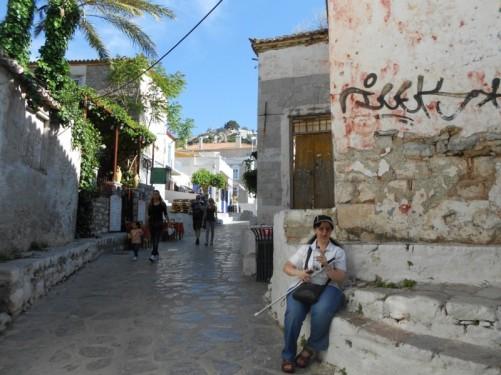 Tatiana sitting on a wall, a back street in Hydra.