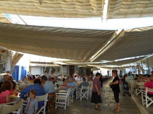 People eating and drinking at covered tables by the harbour.