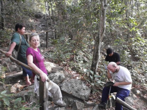 Tony resting at the side of a flight of rock steps on the Uncle Dennis Trail. A woman, visiting from Essex, England, and two Amerindian men, guides from Annai, are with him.