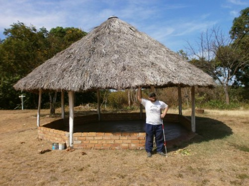Tony by a large round shelter with a thatched roof. Some kind of meeting hut.