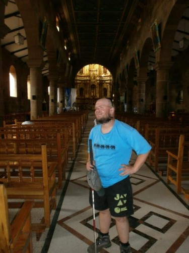 Tony inside Santa Cruz Cathedral. Looking along the main aisle towards the altar. Rows of wooden benches and stone columns down both sides.