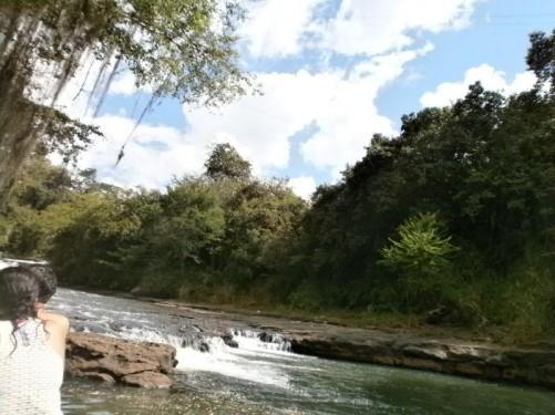 The rocky Quebrada Curití river near the Pozo Azul (Blue Lagoon). Trees and dense vegetation line the far bank.