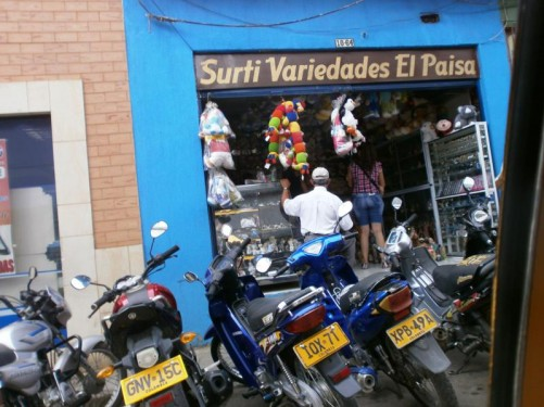 Back in the town centre outside a shop selling various items including ornaments, watches, sun glasses and stuffed toys. A row of motorbikes are parked in front.