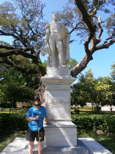 Tony next to a white marble statue of Simón Bolívar in the grounds of Quinta de San Pedro Alejandrino.