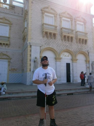Tony outside the Heredia Theatre. The exterior is made of white marble and decorated with statues. It was built in 1911 and restored in 1998.
