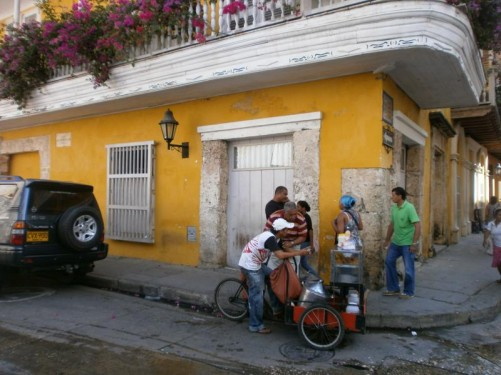 The street below the same house. A man selling food from a cart. Pedestrians passing by.