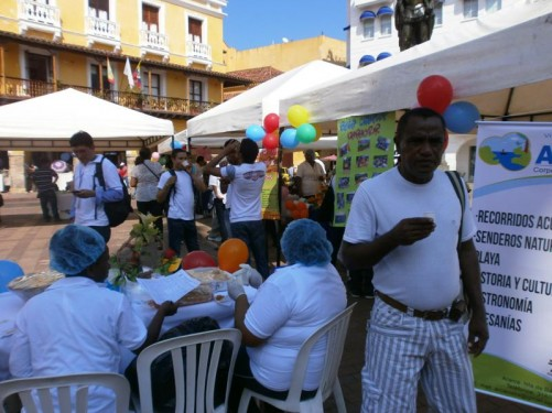 Plaza de los Coches (Carriage Square). Tables around the sides of the square. Food is being served from the tables. A local food day, showing work from art students.