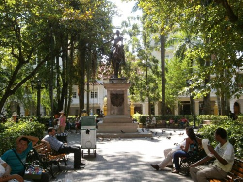 Plaza de Bolívar, a square and park in the old city. In the centre is a statue of Simon Bolívar on horseback. There are people sitting on benches around the sides. The square is surrounded by some of the city's most elegant colonial buildings, including the Palace of the Inquisition.