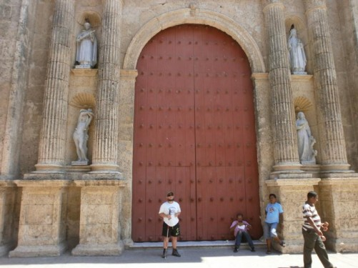 Tony in front of the cathedral's large wooden door. At each side are pairs of stone columns with statues in between them.