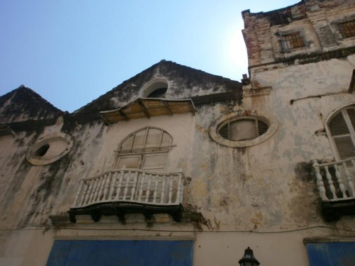 Looking up at the façade of an old building with small decorative balconies.