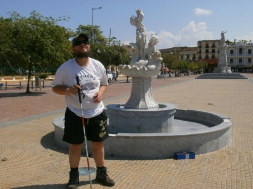 Tony by a marble fountain. It depicts a fish and two cherub-like children inside a large sea shell. Located near the port.