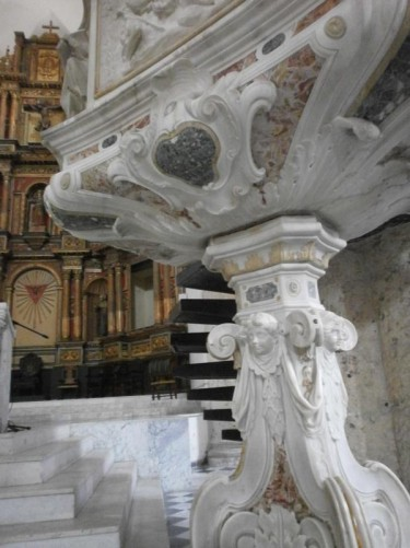 The decorative carved-marble base of the pulpit near the main altar.