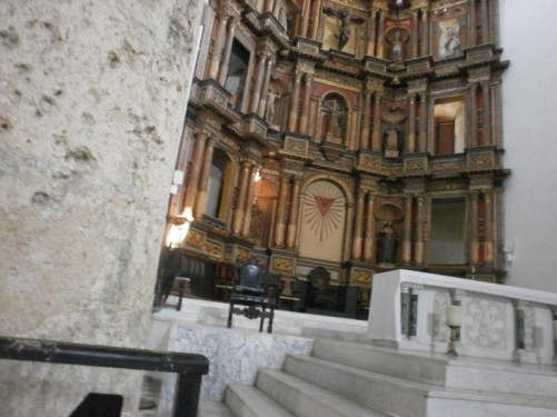 The main altar. Decorated in red and gold. Statues in alcoves, plus a depiction of Jesus on the cross in the centre top.