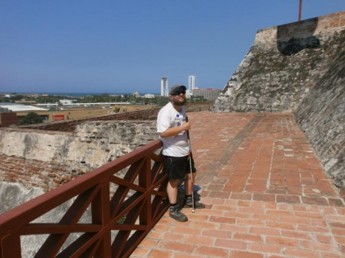 Tony by a sloping defensive wall at the fortress. Again views across the city and the sea in the distance.