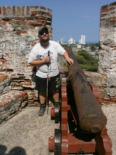 Tony touching a rusty canon pointing through the fortress walls.
