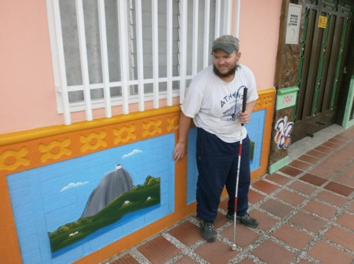 Colourful murals of Guatapé Rock painted along the lower external wall of a building.