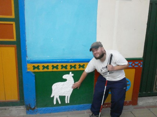 Tony touching a mural of a sheep on the wall of a building.