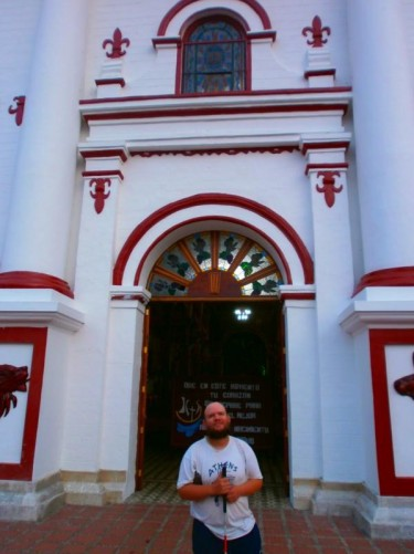 Outside the main doorway into the church. The church is attractively painted in red and white.