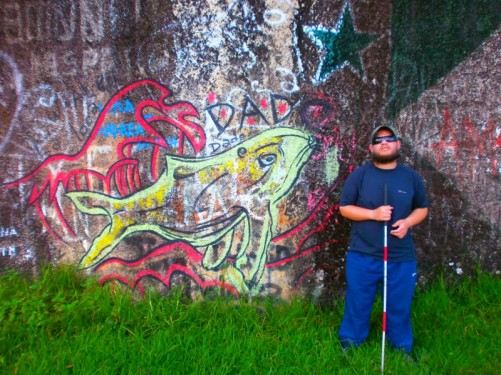 Tony at the foot of the rock. The rock wall immediately behind him has been spray-painted with graffiti.