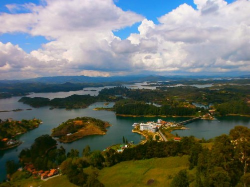 View from Guatapé Rock. Probably at the first viewing level, about half way up. A patchwork of lakes interspersed with wooded land below. Mountains rising in the far distance.