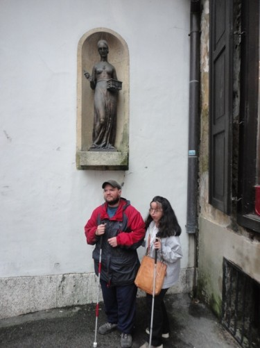 Tony and Tatiana below a statue of Dora Krupic holding a key and box. The statue is inside an alcove built into the outer wall of the Stone Gate. Dora Krupic is a fictional character from the novel 'The Goldsmith's Gold' written in 1872 by August Senoa.