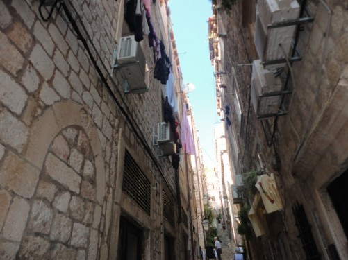 A side street off the Stradum. It is narrow with a steep flight of steps. Washing hanging above from the windows of houses.