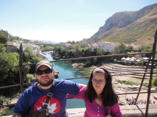 Tony and Tatiana sitting at the side of the bridge. The turquoise coloured Neretva river down below.