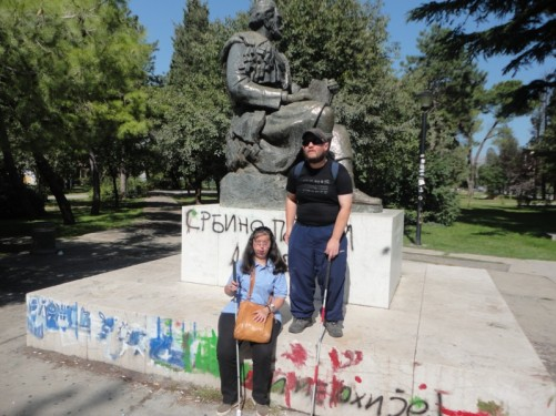 Tony and Tatiana in a park by a seated statue of Petar Njegos.
