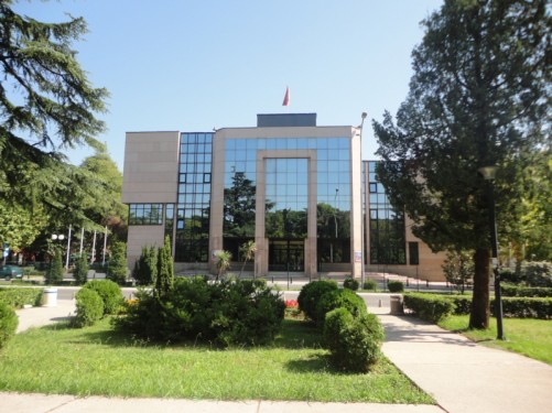 Outside a modern-looking glass-fronted office building with the Montenegrin flag flying above.