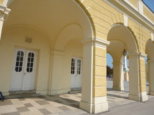 At the side of the courtyard. A colonnade creating a covered walkway around the edge of the yellow and white palace building.