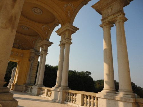 An arcade in one of the Gloriette's two wings. A walkway with stone arches supported by columns at either side.
