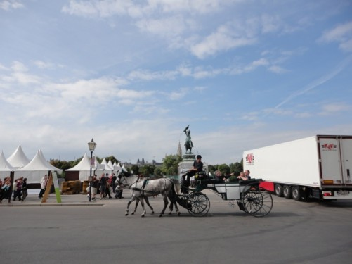 View across Heldenplatz. Tourists riding in the back of a horse and cart (fiacre). The Archduke Charles equestrian statue in the background.