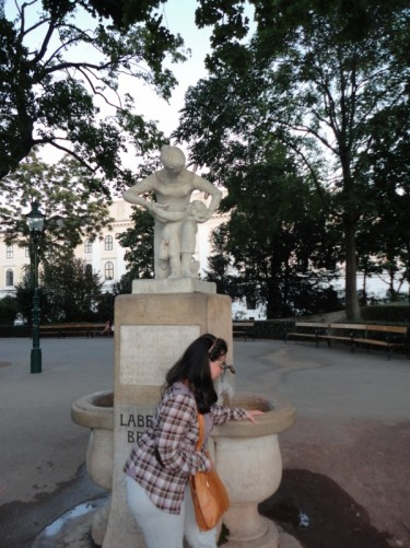 Tatiana by a statue and drinking fountain in Stadtpark during the evening.