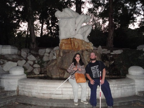 Tony and Tatiana sitting in front of a water feature and sculpture in Stadtpark. The stone sculpture appears to be of two men trying to lift a boulder.