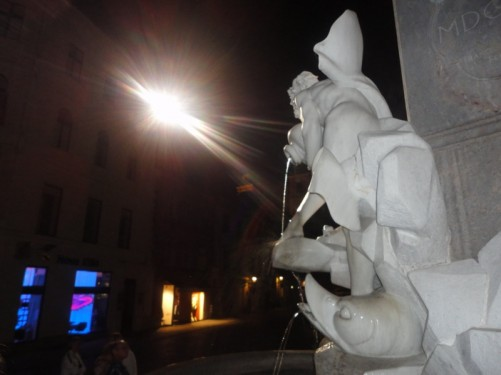 Fountain of the Three Carniolan Rivers (or Robba's Fountain) located in Town Square (Mestni trg). It is dark but detail on the fountain is well-lit. A fish with water flowing from its mouth and a man holding an urn can be seen.