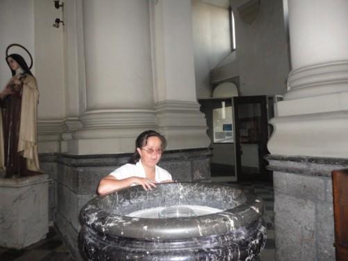 Tatiana touching a marble font inside the church.