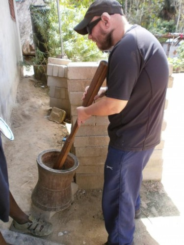 Tony holding a wooden pole which is inside a wooden vessel - it is used for grinding cassava - like a mortar and pestle.