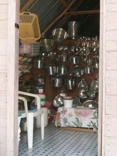 Looking into a Maroon village building. A large collection of pots and pans hanging on the wall.