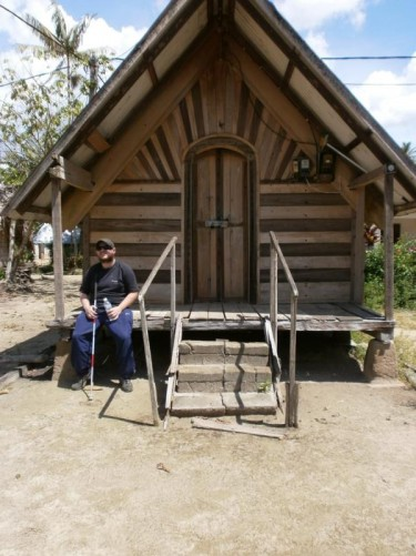Tony sitting outside a wooden hut.