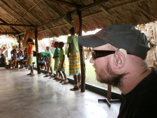 Tony sitting watching the villagers  perform several traditional dances. The dances represent slave life in Suriname, when it was Dutch Guiana.