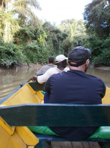 Travelling along a narrower stretch of river in the canoe. Tony sitting in the seat immediately in front.