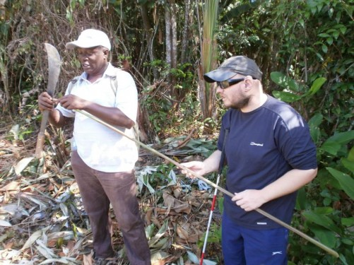 Tony with a man who is holding a machete and long straight stick. He is a local Surinamer, a Maroon, who works at the eco-lodge and lives in the Maroon village.