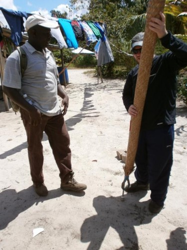 Tony holding a long pole made from woven plant fibre at the Amerindian village.