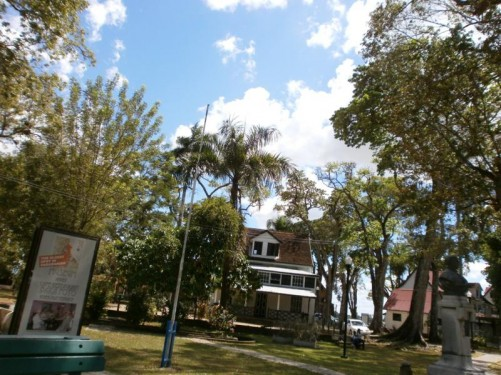 A grassy area between the palm garden and the river. More colonial-era houses. A bust can be seen to the right. This is of Titus van Asch van Wijck (1849 - 1902) who was governor of Suriname between June 1891 and May 1896.