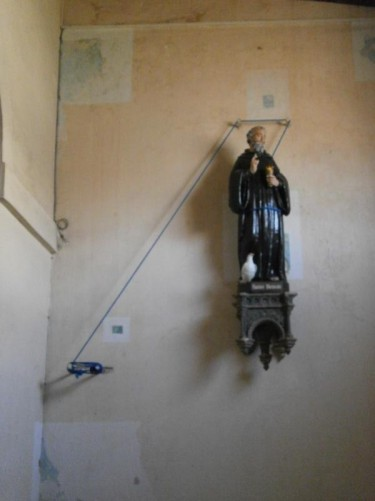 A small statue of St Benoît (Benedict) mounted on a wall inside the cathedral.